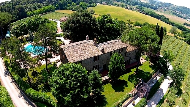 Drone view of the rear of the main house, principal fire pit, swimming pool, bocce court, guesthouse and wrap-around-olive groves. The tennis court is blocked by trees